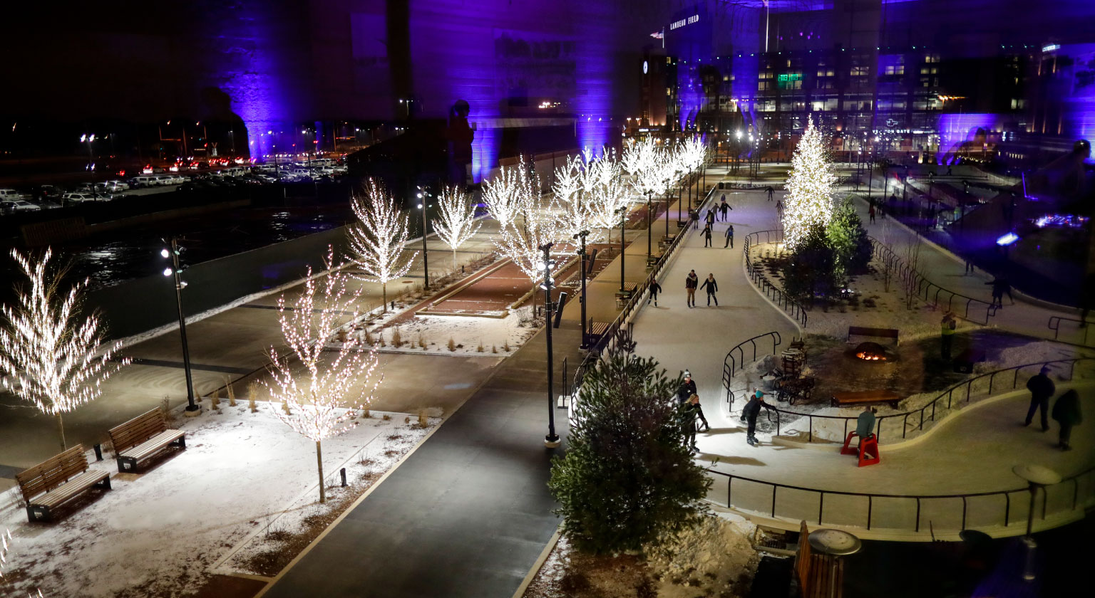 View of Ice Skating Rink at Titletown. Decorated white trees around the perimeter.