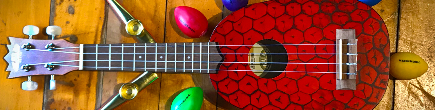 Red ukulele surrounded by egg shakers and kazoos on a wooden floor.