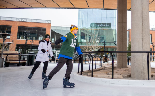 Young man wearing Packers jersey skating with women in white coat on Titletown's ice rink.