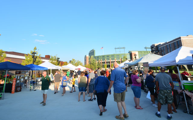 Tents in front of Lambeau Field for Titletown's Night Market. Individuals browsing at tents.