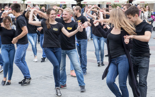 Group of young adults wearing black t-shirts and jeans dancing outdoors.