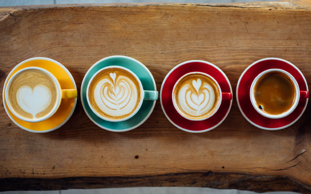 Shots of coffee beverages in multi-colored mugs lined up on a piece of wood.
