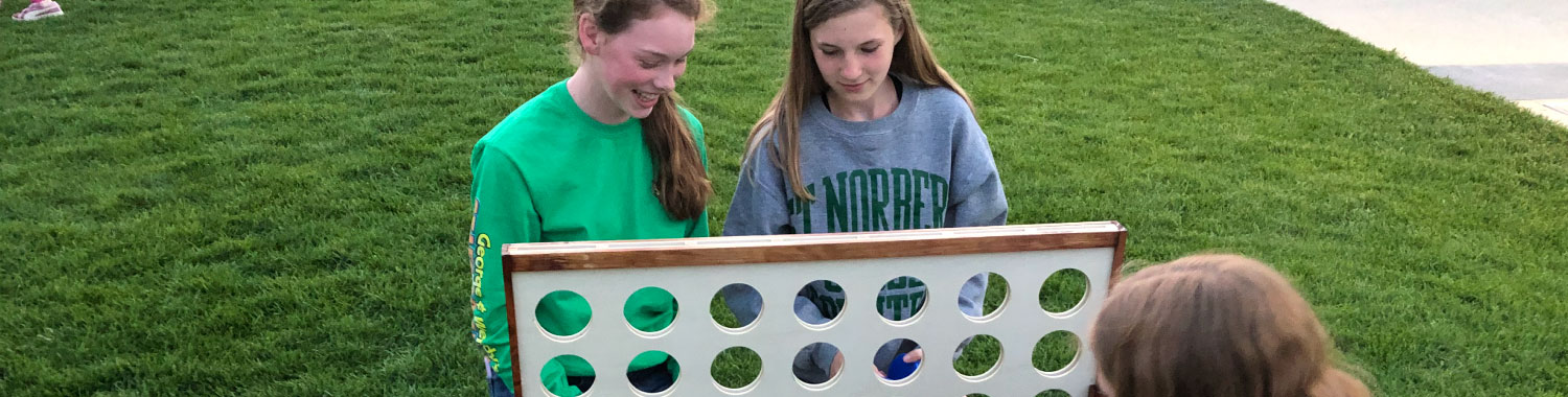 Three girls playing giant Connect 4 on the base of Ariens Hill in Titletown.