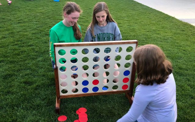 Three girls playing giant Connect 4 on the lawn in front of 46 Below.