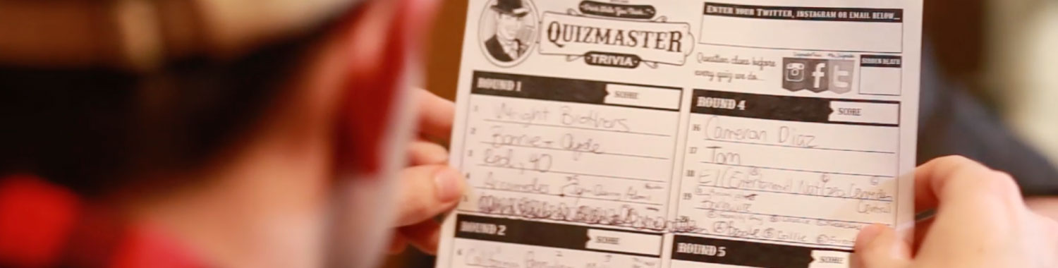 Blurred man in plaid shirt and tan hat holding a completed Quizmaster trivia response form.