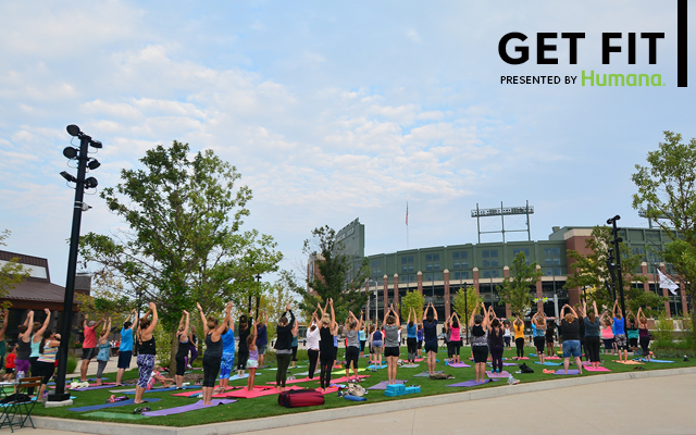 Large group doing Yoga (arms raised) on the Great Lawn at Titletown with Lambeau Field in the background. Presented by Humana.