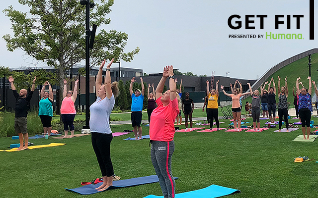 Group of people doing Yoga on the Great Lawn at Titletown. Presented by Humana