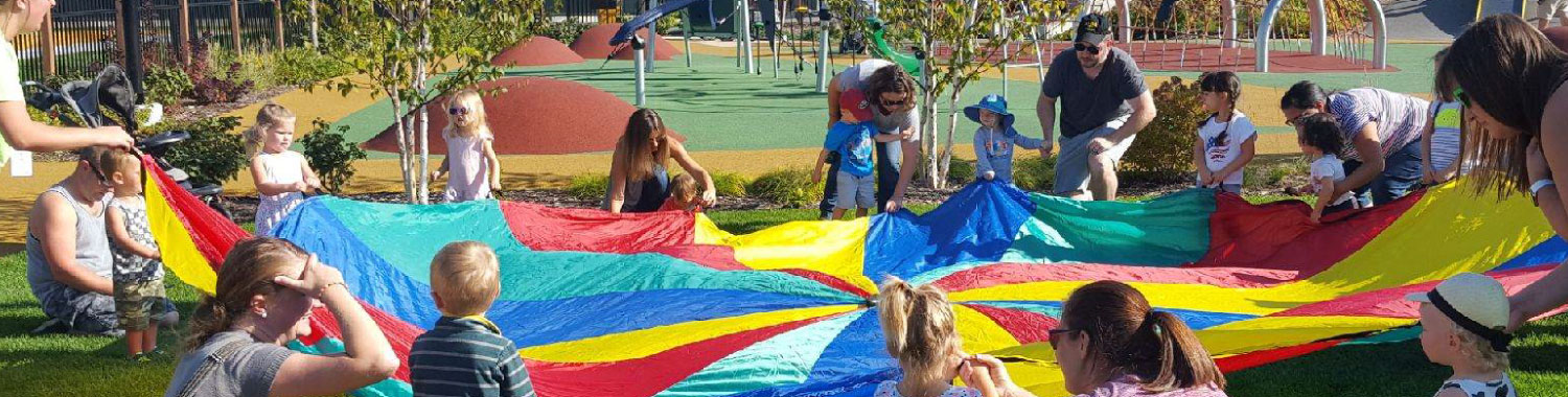 Group of children and adults around a multi-colored parachute in the Titletown playground with the football field in the background.