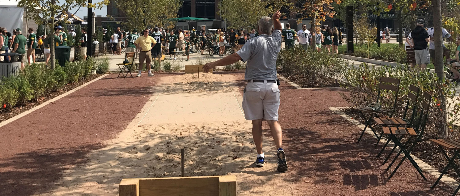 Man throwing horseshoe in Titletown game court. Lambeau Field in background.
